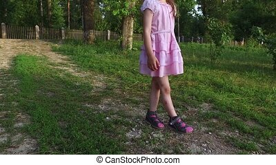Girl child walking slowly on lawn. Feet girl scratched. Summer sunny evening.