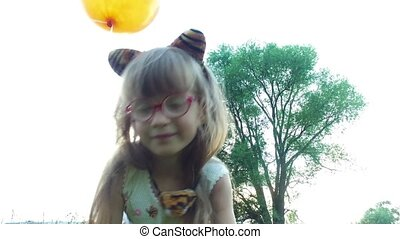 Girl child with glasses shows a cat. The girl hisses like a cat's and shows claws.