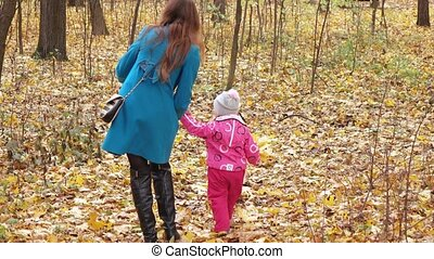 Girl child with mom in the forest