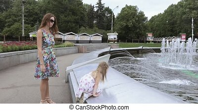 Girl child with mother near the fountain