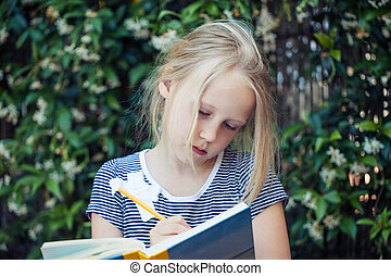 Girl child with notebook outdoors portrait. Girl writing