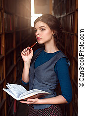 Girl choose book with notebook in her hands.