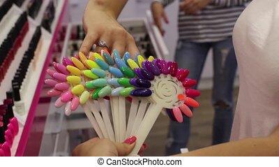 Girl chooses a color nail polish