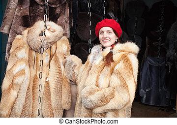 girl chooses a fur coat at market