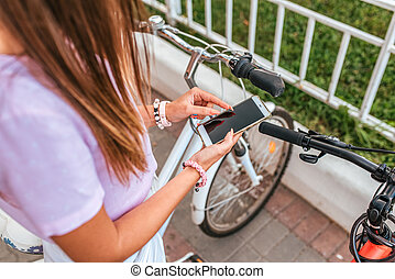 Girl chooses a route in summer in city on smartphone. Bicycle parking in summer in city. Bicycles for rent. Online application to Internet, booking vehicles, locking bikes. Girl's hands, long hair.