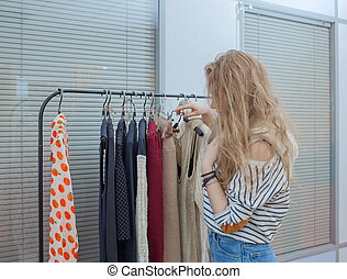 Girl chooses clothes in a boutique.