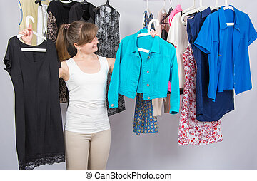 Girl chooses clothes in her wardrobe