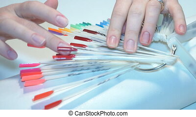 girl chooses color of Polish for manicure. testers nail Polish