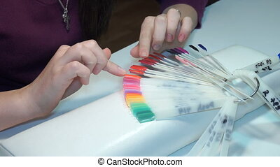 girl chooses color of Polish for manicure. testers nail...