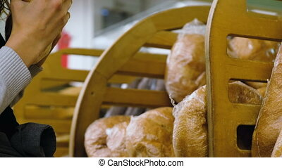 Girl chooses fresh bread in the shop Close-up, 4k.