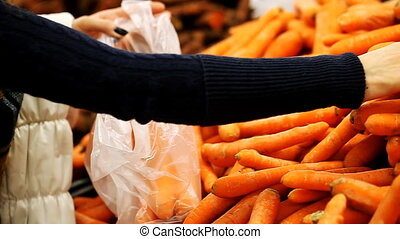 Girl chooses juicy carrots at the supermarket