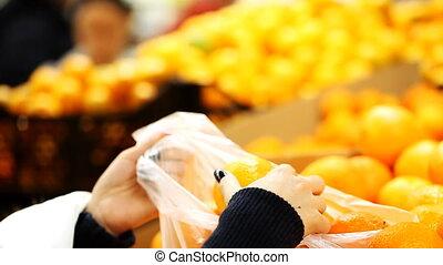 Girl chooses oranges in a supermarket