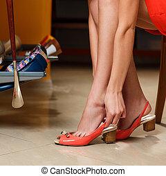 Girl chooses shoes in wardrobe room.