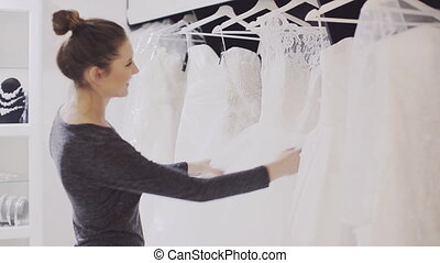 girl chooses wedding gown at bridal boutique - Young woman...