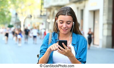 Girl choosing and listening to music outdoor - Front view of...