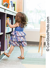 Girl Choosing Book From School Library