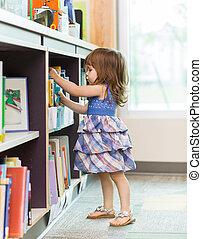 Girl Choosing Book From School Library - Full length side...