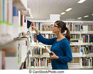 female college student taking book from shelf in library. Horizontal shape, side view, waist up, copy space