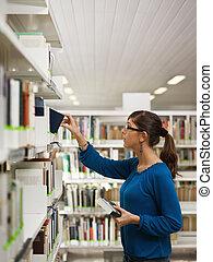 girl choosing book in library