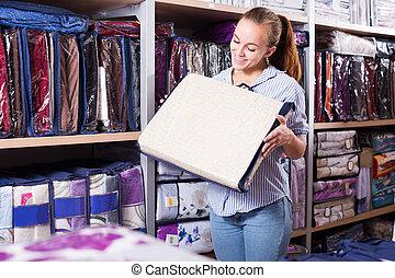 Girl choosing new bed linen - Happy young girl choosing new ...