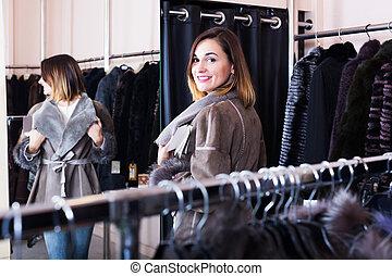 Girl choosing sheepskin coat