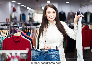 Girl choosing trousers at boutique