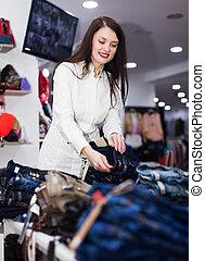 Girl choosing trousers at market