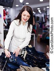 Girl choosing trousers at shop