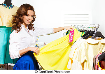 Girl choosing yellow skirt during sale in shop