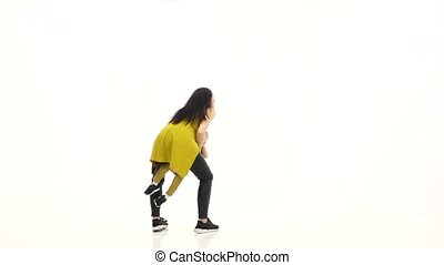 Girl circles around her son, he laughs. White background....