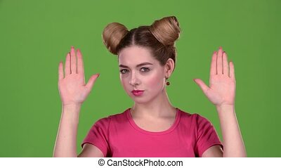 Girl claps her hands and closes her face. Green screen