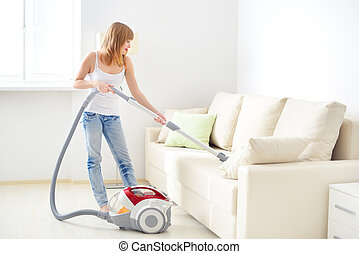 girl cleaning sofa - Attractive girl with vacuum cleaner