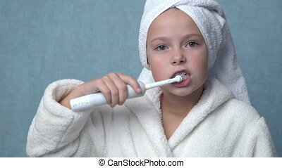 girl cleaning teeth with electric toothbrush