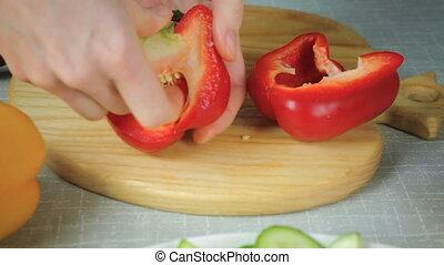Girl cleans ripe red pepper at the board