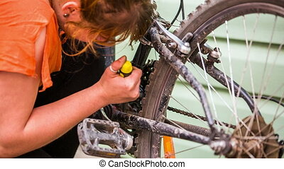 Girl cleans the bike with a screwdriver - The girl cleans...