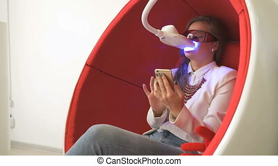 Girl client sitting in chair during whitening