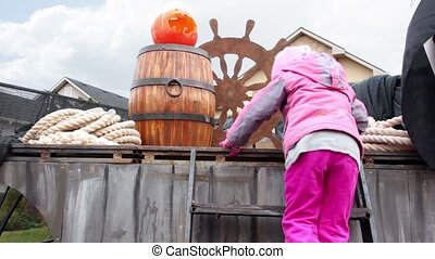 girl climbes by stairs on stage where is pumpkin of Halloween