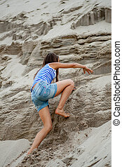 girl climbing on the sand - little girl climbing on the sand...