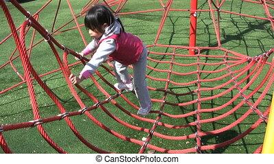 Girl Climbing Web At Playground - A cute Asia girl...