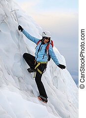 Girl climbs on a glacier in Iceland