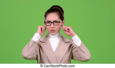 Girl closes her ears from a sharp noise. Green screen. Slow...