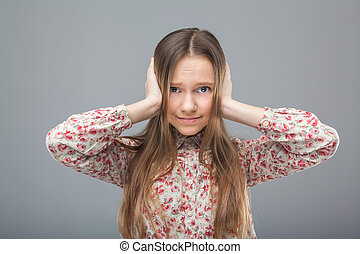 Girl closes her ears with hands