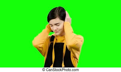 Girl closes her ears with her hands. Green screen