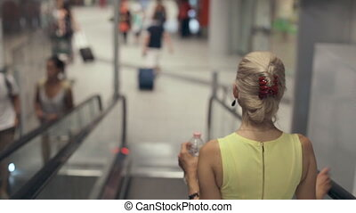 Girl clothed in a dress coming down the escalator