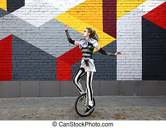 Girl clown performing with a unicycle - Girl clown in circus...