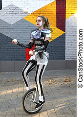 Girl clown rides a unicycle and juggles balls outdoors