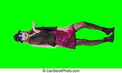 Girl clown standing on green background dressed in red dress...