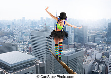 Girl clown walks on a rope over the city
