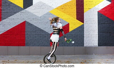 Girl clown with white rose riding a unicycle outdoors