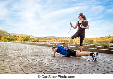 Girl coach training hard a man through push ups - Beautiful...